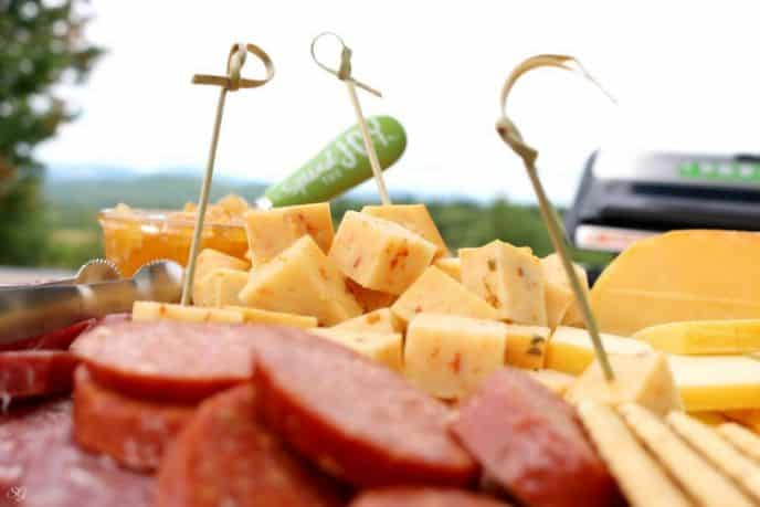 Smoked cheese platter with meat and crackers.