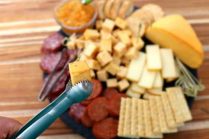 Smoked cheese on the barbecue grill served on a platter with smoked meat, crackers and jam.