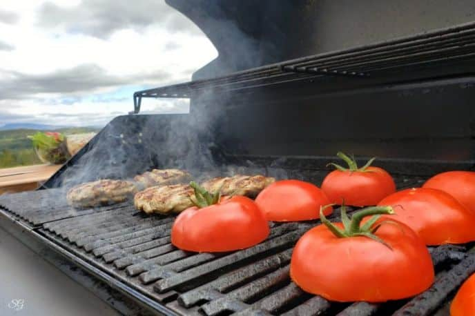 Grilling turkey burgers and tomatoes for buns the barbecue grill.