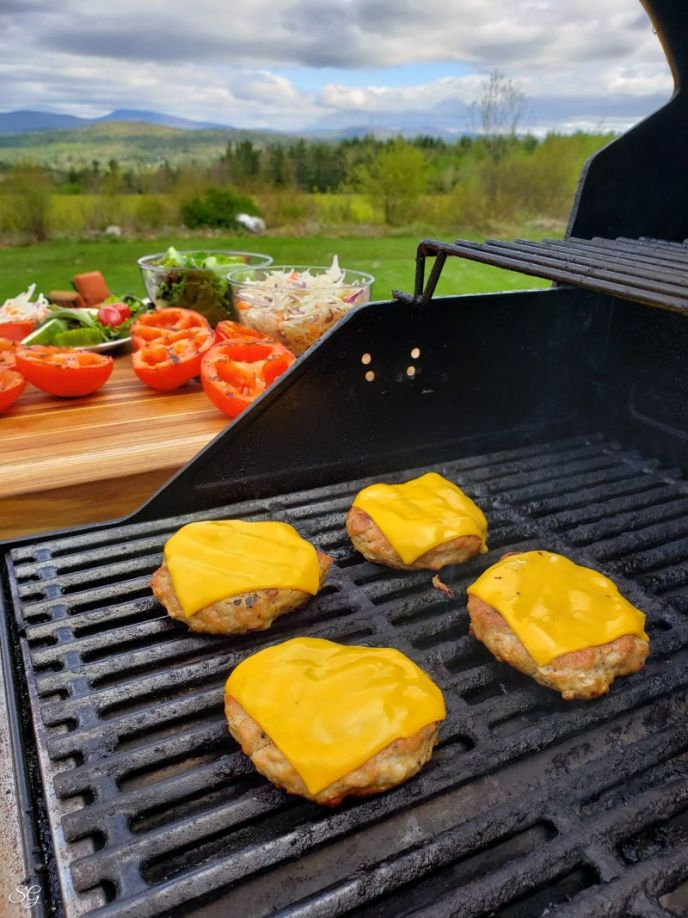 Grilling turkey burgers with cheese on the barbecue grill.