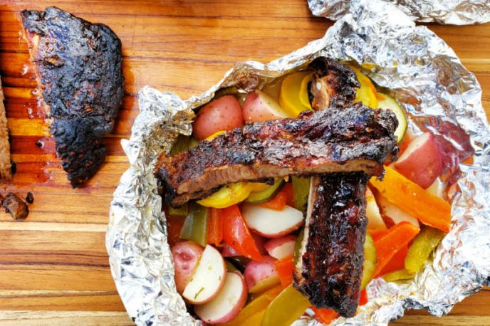 Barbecue pork ribs and vegetable grilled foil packs.