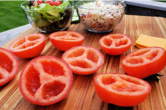 Halved tomatoes with seeds removed to use as turkey burger buns for a low carb recipe.