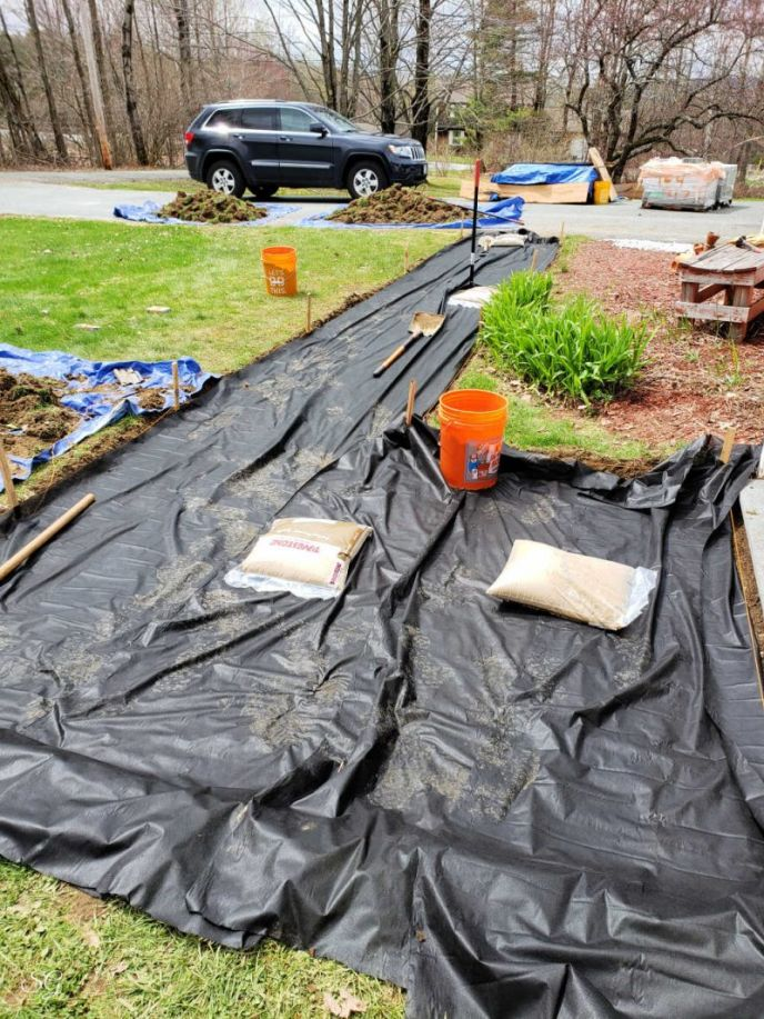 Putting down landscape fabric under the sand of our paver walkway DIY project.