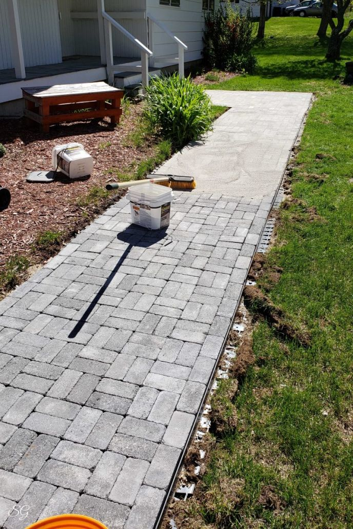 Installing polymeric sand on a paver walkway DIY project.