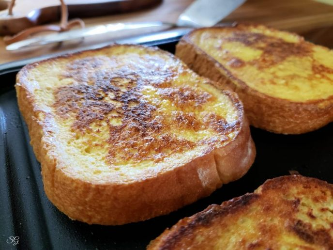 French toast browning on a skillet, cooking to make French toast dessert roll ups. #minustheshell