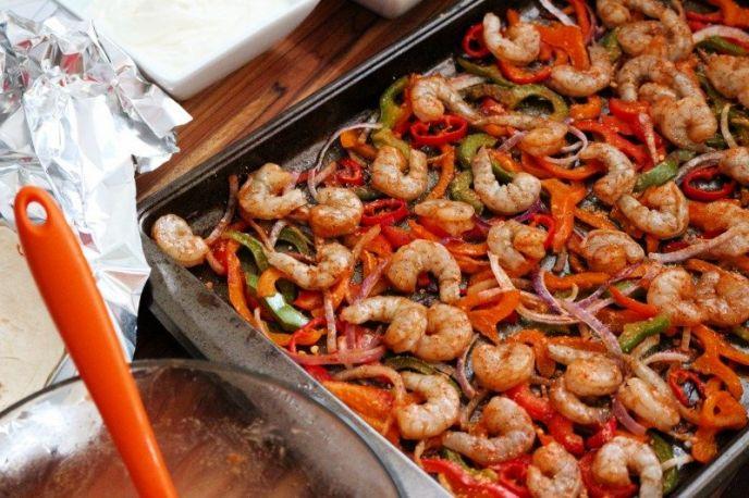 Making sheet pan shrimp fajitas on one pan with veggies and shrimp